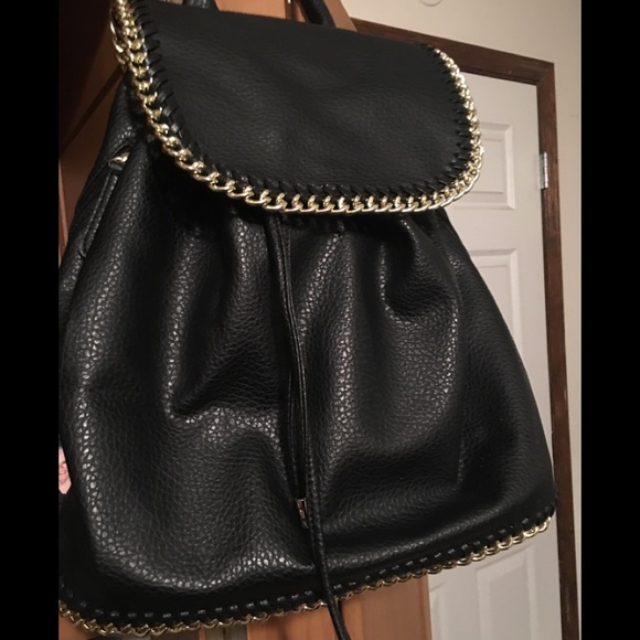 90f042bdc52 Faux leather backpack with gold chain trim.